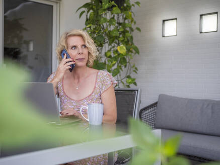 Thoughtful female professional talking on phone while sitting with laptop working at home - LAF02497