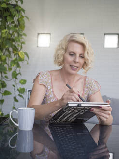 Blond businesswoman using laptop while sitting at home office - LAF02503