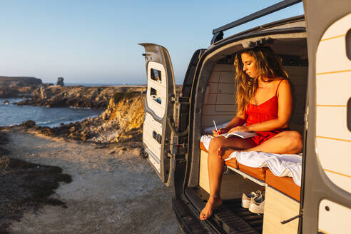 Woman writing in book while sitting in camper van against at beach - DCRF00978