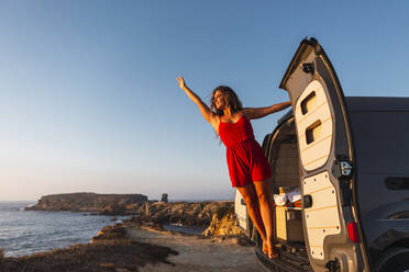 Smiling woman with hand raised standing while hanging on camper van door at beach - DCRF00981