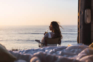 Young woman drinking white wine while sitting on chair by camper van at beach during sunset - DCRF00993