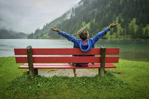 Woman sitting on bench with arms outstretched at lakeshore while looking at mountains - DIKF00544