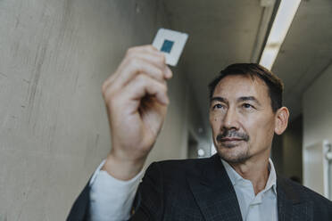 Businessman holding business chip while standing at clinic corridor - MFF06303