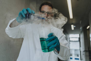 Scientist mixing liquid solution in flask while standing at clinic corridor - MFF06306