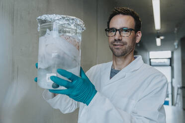 Scientist holding preserved human brain beaker while standing at clinic corridor - MFF06309