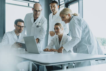 Team of doctors and scientist using laptop while working at office - MFF06318