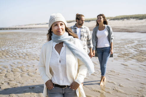 Smiling woman looking away while walking with couple holding hands in background at beach - UUF21687