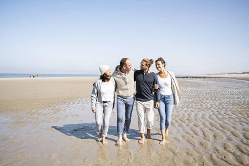Family talking while walking together at beach - UUF21705