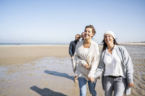 Smiling women holding hands while walking with men in background at beach - UUF21717