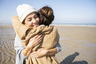 Daughter and mother embracing each other while standing at beach - UUF21726