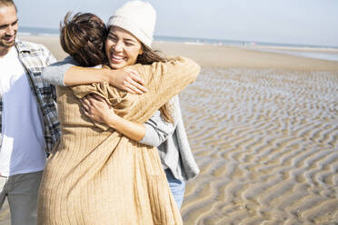 Mother and daughter embracing while standing by man at beach - UUF21729