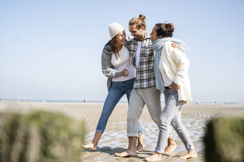 Smiling family talking while walking at beach together - UUF21741