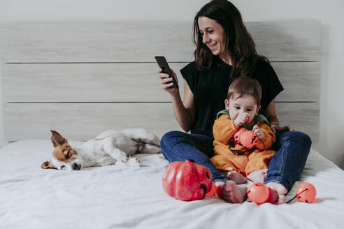 Mother text messaging on smart phone while son playing with toys sitting at home - EBBF00877