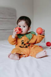Cute male toddler playing with pumpkin halloween toy while sitting on bed at home - EBBF00880