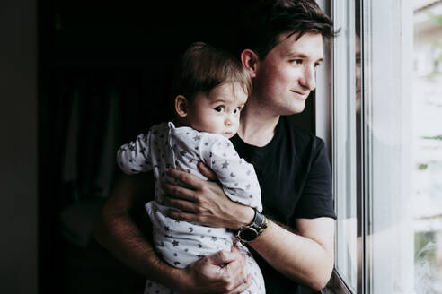 Smiling father carrying son while standing looking through window at home - EBBF00889