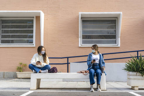 Female friends social distancing wearing protective face mask sitting on concrete bench - ERRF04571