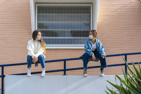 Female friends looking at each other while sitting on railing - ERRF04583