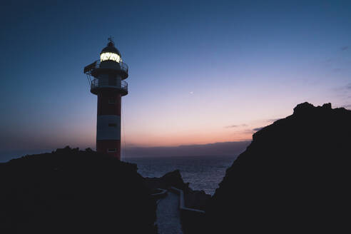 Low angle of spectacular scenery of illuminated lighthouse located on rocky hill near sea against sunset sky in Tenerife - ADSF16672