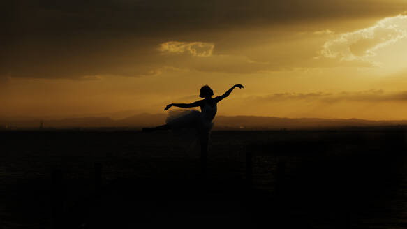Silhouette of elegant flexible female dancer with outstretched arms performing ballet movement against cloudy sundown sky - ADSF16696