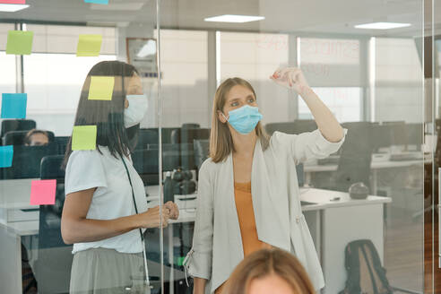 Young female member of business team in protective mask taking notes on glass wall while working with colleagues and searching for solution of business problem in contemporary office - ADSF16723