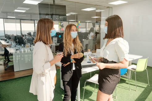 Group of modern young female colleagues in protective masks gathering in contemporary workspace and discussing business ideas while working together during coronavirus pandemic - ADSF16729