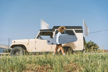 Young woman carrying surfboard by old off-road vehicle on sunny day - DAMF00570