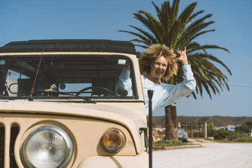 Cheerful blond woman gesturing while sitting in old off-road vehicle on sunny day - DAMF00573