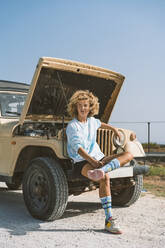 Confident young blond Afro woman looking away while sitting on bumper of broken-down vehicle during sunny day - DAMF00576
