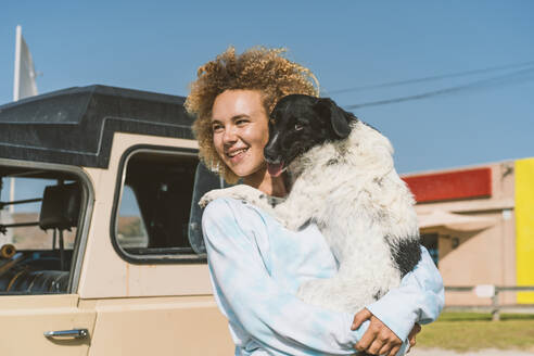 Smiling young blond woman carrying dog while looking away on sunny day - DAMF00579