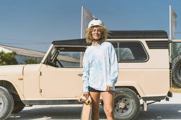 Smiling blond woman wearing helmet holding skateboard while standing against off-road vehicle on sunny day - DAMF00582
