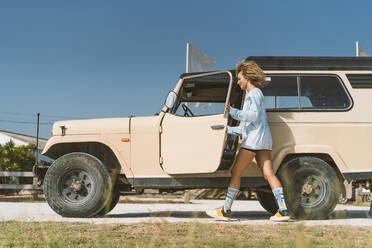 Young Afro woman by old off-road vehicle on sunny day - DAMF00585