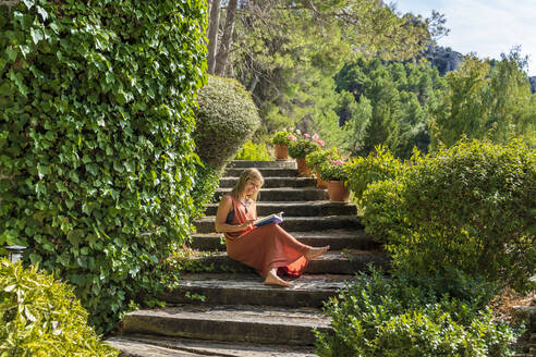 Mature woman reading book while sitting on steps amidst green plants at health retreat during sunny day - DLTSF01380