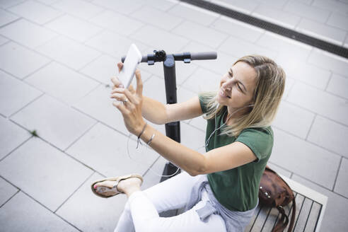 Mid adult woman taking selfie while sitting on bench in city - HMEF01110
