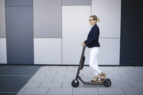 Woman driving electric push scooter on footpath in city - HMEF01116
