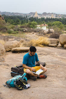 Young man reading book while sitting on land, Karnataka, Hampi, India - JMPF00463