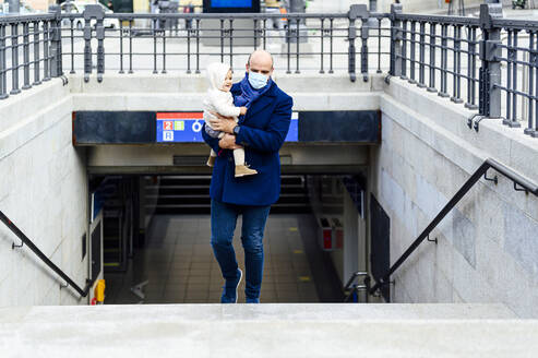 Man with face mask carrying baby while walking on staircase in city - PGF00147
