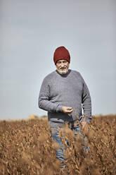 Farmer examining crop while walking in farm against clear sky - ZEDF03961