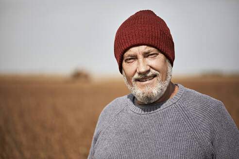 Farmer wearing knit hat smiling while standing at soybean farm - ZEDF03964