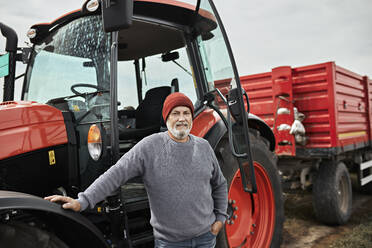Farmer standing by tractor at soybean farm - ZEDF03973