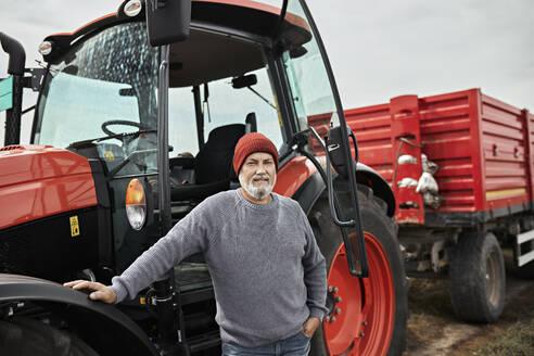 Farmer standing by tractor at soybean farm - ZEDF03973