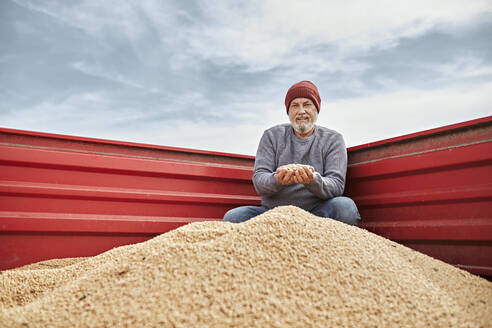 Smiling farmer examining soybean while sitting in tractor against clear sky - ZEDF03976