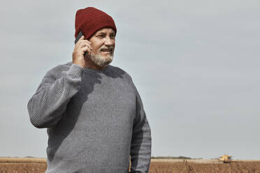 Farmer talking on mobile phone while standing at farm  - ZEDF03979