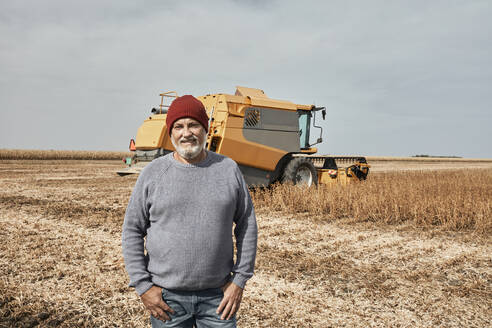 Smiling farmer standing against tractor harvesting crop at farm - ZEDF03982