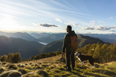 Hiker standing by dog while looking at mountain range during sunset - MCVF00631