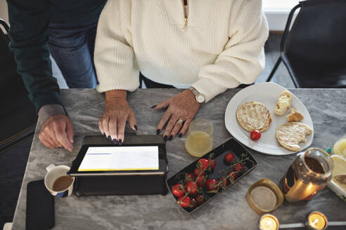 High angle view of senior couple using digital tablet while sitting by dining table in living room - MASF19975