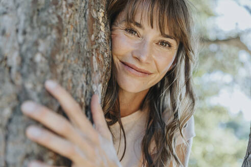 Smiling mature woman leaning on pine tree in public park - MFF06405