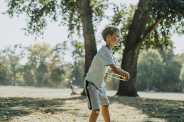 Little boy throwing frisbee ring while standing in public park on sunny day - MFF06408