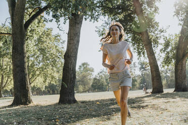 Mature woman jogging in public park on sunny day - MFF06411