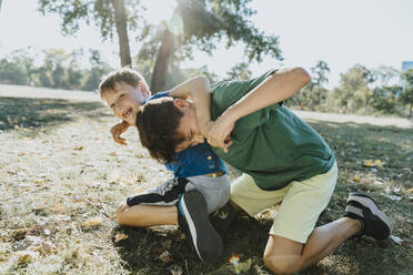 Smiling brothers embracing each other in public park on sunny day - MFF06420
