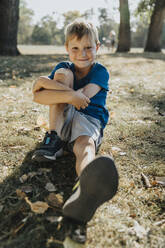 Smiling boy sitting in public park on sunny day - MFF06423